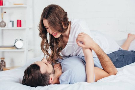 Photo for Selective focus of young loving couple gentle embracing in bed - Royalty Free Image