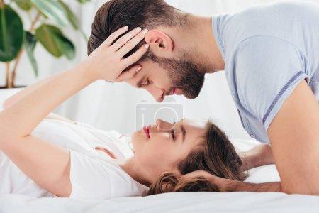 Photo pour Foyer sélectif de jeune couple aimant embrassant doucement et regardant dans les yeux au lit - image libre de droit