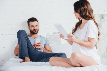 young couple sitting on bed with gadgets and talking in bedroom