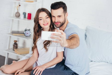 Photo pour Jeune couple assis sur le lit dans la chambre et prise selfie sur smartphone - image libre de droit