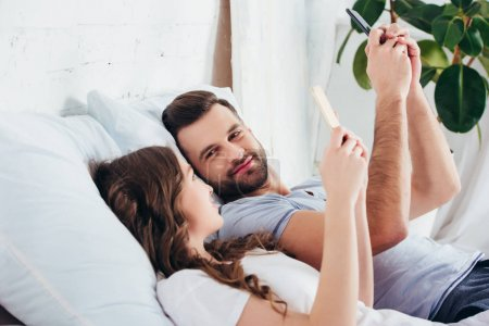 young couple relaxing in bed while using smartphones and looking at each other