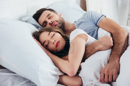 adult couple sleeping on soft white bedding in bedroom