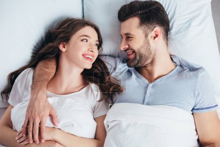 boyfriend and girlfriend lying on soft white bedding in bedroom