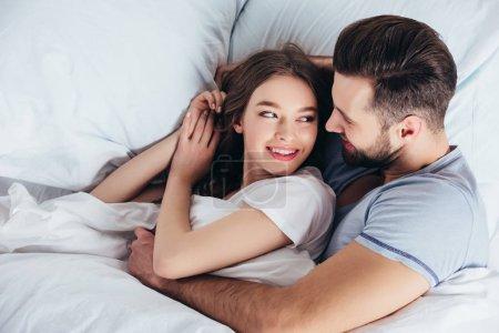 Photo pour Jeune couple aimant câlin doux au lit et regardant dans les yeux - image libre de droit