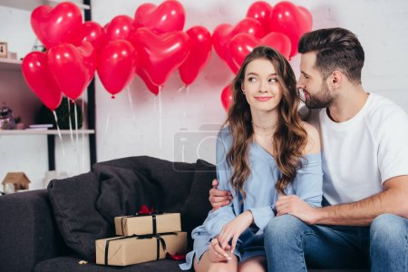 happy man looking at woman in room decorated for st valentine day