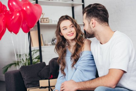 happy man looking at woman in room decorated with heart-shaped balloons