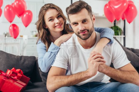 happy young girlfriend embracing boyfriend in room with heart-shaped balloons