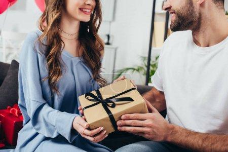 Photo pour Vue recadrée de jeune couple heureux tenant boîte cadeau avec ruban - image libre de droit