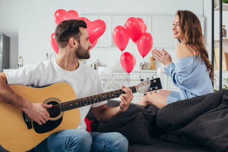 loving couple celebrating st valentine day while young man playing acoustic guitar