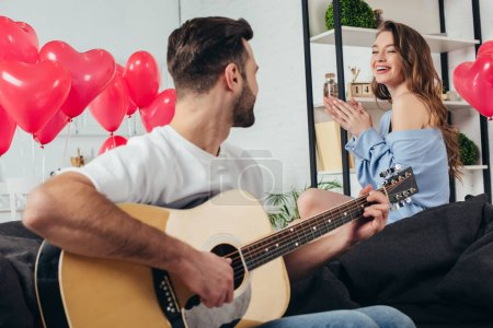 happy couple celebrating st valentine day while young man playing acoustic guitar