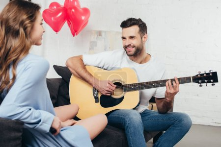 young man playing guitar to smiling girlfriend with heart-shaped balloons on background