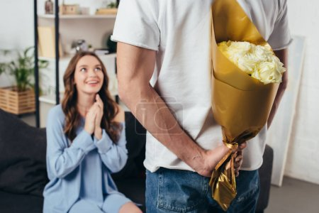 selective focus of young man holding bouquet of roses behind back while surprised smiling girl sitting with folded hands on sofa