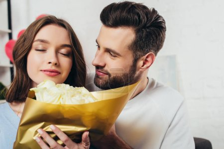 smiling girl with closed eyes smelling roses bouquet near boyfriend