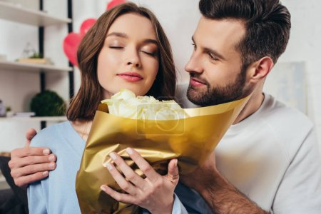 admiring girl with closed eyes smelling roses bouquet near boyfriend
