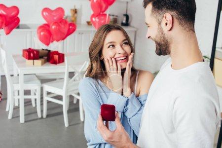 Photo pour Foyer sélectif de fille surprise toucher le visage tandis que l'homme faire la demande en mariage à la Saint-Valentin - image libre de droit