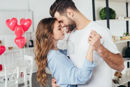 selective focus of beautiful happy couple dancing on st valentine day with heart-shaped balloons on background