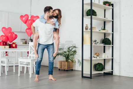young man giving piggyback ride to smiling girlfriend in furnished room with st valentine day decoration