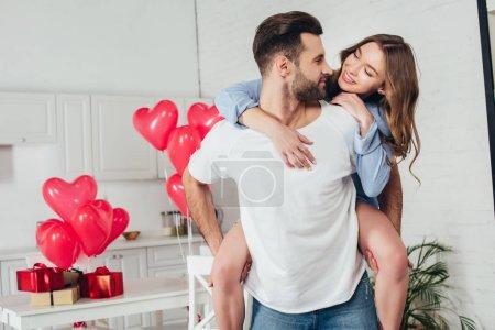 Photo pour Jeune homme donnant piggyback tour à sourire petite amie à la maison avec st décoration Saint-Valentin - image libre de droit