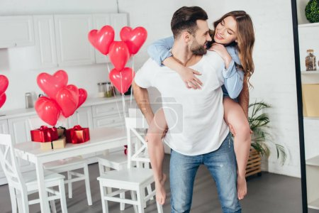happy couple piggybacking at home in room with st valentine day decoration