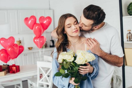 happy girl holding roses bouquet with closed eyes while boyfriend kissing cheek and embracing girlfriend