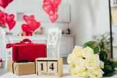 gift boxes with ribbons, roses bouquet and calendar with st valentine day date on table with heart-shaped balloons on background