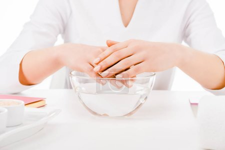 Photo pour Recadrée vue de manucure tenant par la main au-dessus de bain verre isolé sur blanc - image libre de droit