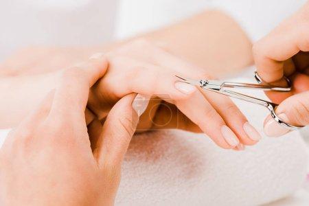 Photo pour Recadrée vue de manucure main doucement tout en cuticule de coupe - image libre de droit
