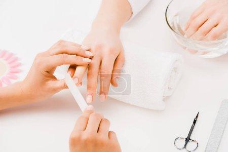 Photo pour Recadrée vue de manucure ongles avec la lime à ongles de dépôt - image libre de droit