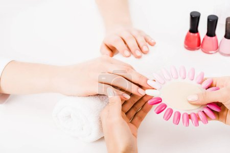Photo pour Vue recadrée de manucure tenant palette de vernis à ongles tout en choisissant la couleur - image libre de droit