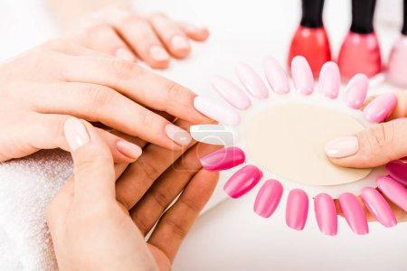 Vista parcial de la manicura sosteniendo la paleta de esmalte de uñas mientras que la mujer elige el color