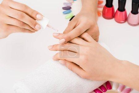 Photo pour Recadrée vue de manucure tenant le doigt lors de l'application de vernis à ongles - image libre de droit
