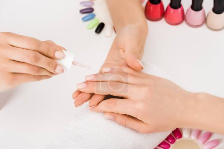Photo for Partial view of manicurist using color palette and applying nail polish - Royalty Free Image