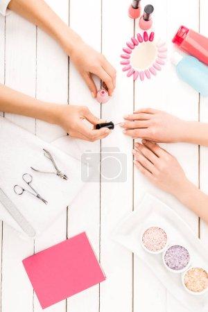 Photo pour Vue de dessus de manucure application de vernis à ongles rose - image libre de droit