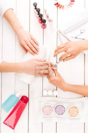 Foto de Vista parcial de manicurista con cortauñas mientras trabaja con el cliente - Imagen libre de derechos