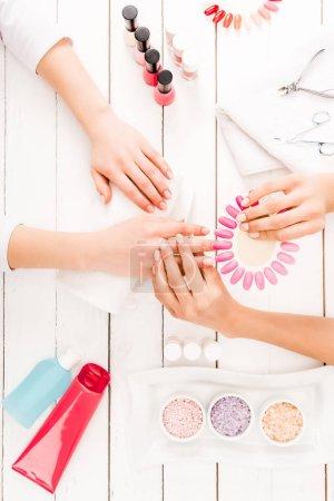 Foto de Vista superior de manicurista eligiendo color de esmalte de uñas - Imagen libre de derechos