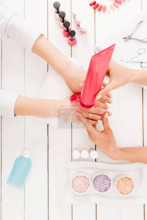 Photo for Top view of manicurist using hand cream on wooden surface - Royalty Free Image