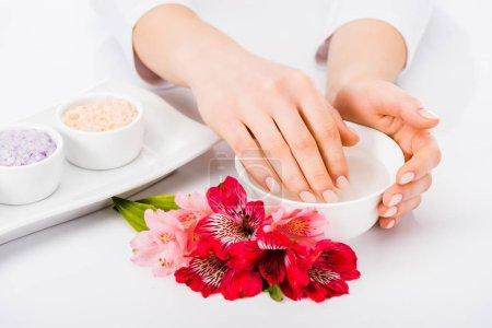Photo pour Vue partielle de la femme prendre bain d'ongles avec des fleurs - image libre de droit