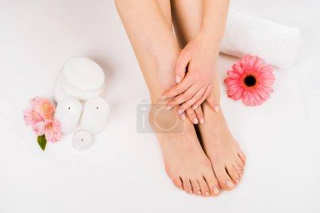 Photo pour Coup partielle de la femme assise sur la surface blanche et toucher les jambes - image libre de droit