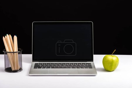 Photo for Apple, laptop with blank screen and pencils isolated on black - Royalty Free Image