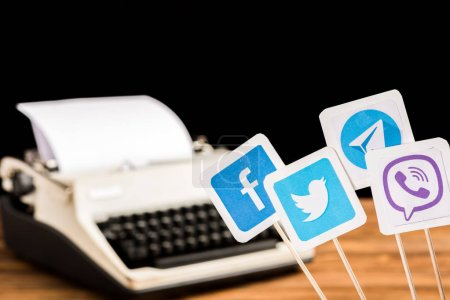 selective focus of facebook, twitter, viber and telegram icons with typewriter on background