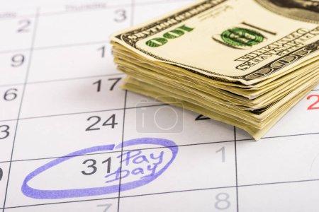 """Photo pour Mise au point sélective des billets en dollars, calendrier portant le numéro 31 et le lettrage """"jour de paye"""" - image libre de droit"""