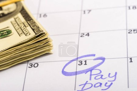 Photo for Selective focus of dollar banknotes, calendar with marked number 31 and 'pay day' lettering - Royalty Free Image
