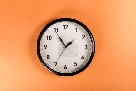 top view of round clock isolated on orange