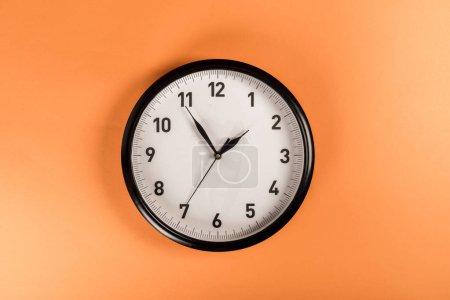 vue de dessus de l'horloge ronde isolée sur orange