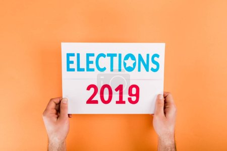 cropped view of man holding card with 'elections 2019' lettering isolated on orange