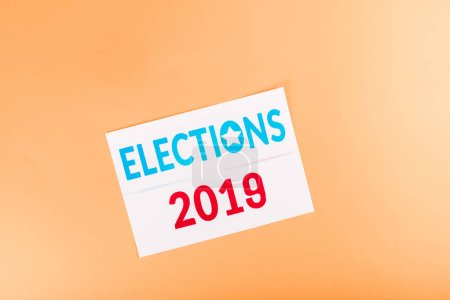 top view of card with 'elections 2019' lettering isolated on orange