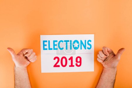 Photo pour Cropped view of man showing thumbs up near card with 'elections 2019' lettering isolated on orange - image libre de droit