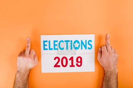 cropped view of man showing middle fingers near card with 'elections 2019' lettering isolated on orange