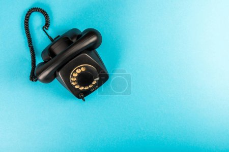 Photo for Top view of black rotary dial telephone isolated on blue with copy space - Royalty Free Image