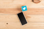 top view of twitter icon and smartphone with blank screen on wooden table